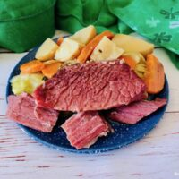 Featured image showing a plate full of veggies and the Crock pot corned beef and cabbage ready to eat.