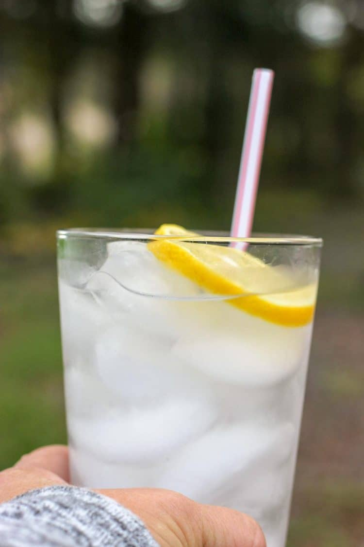 glass with ice, lemon slice and straw.