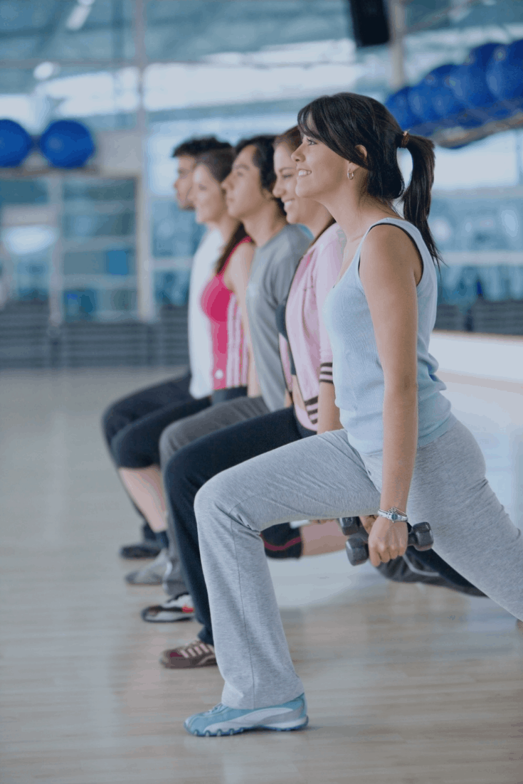 women in a row with weights in gym