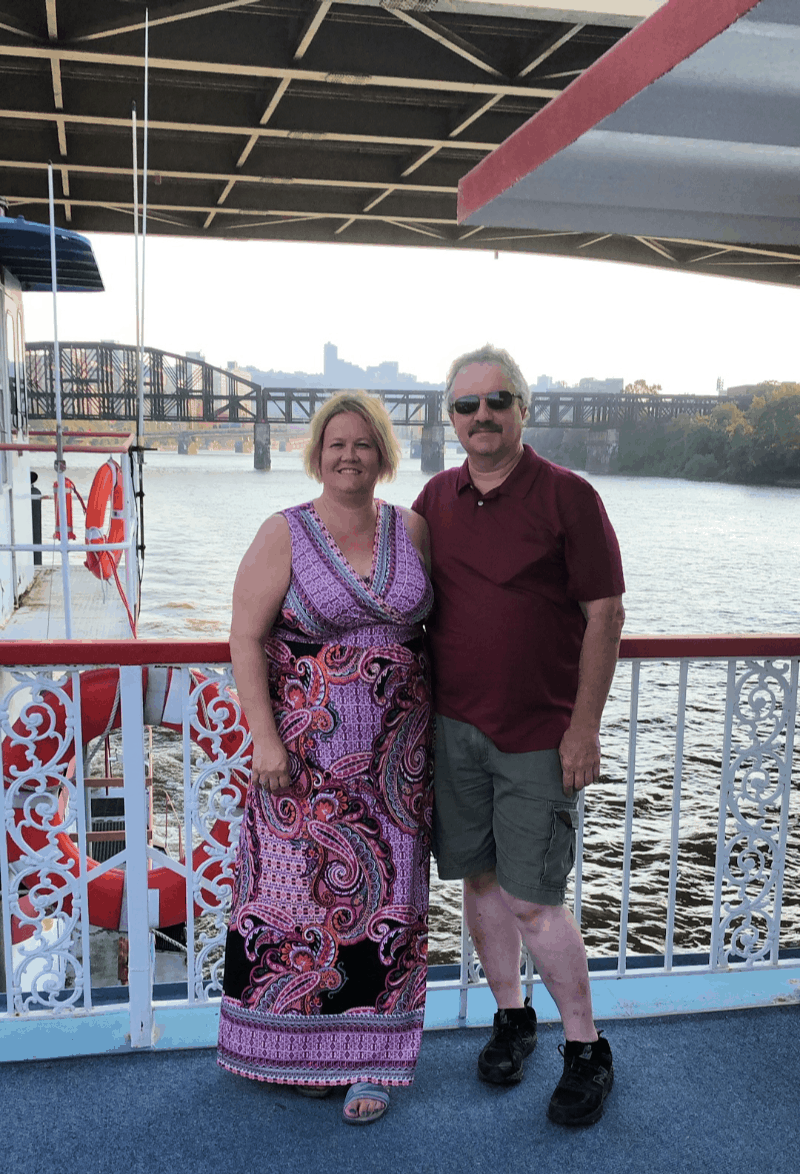 Middle aged couple on a river boat deck with bridge in backgound.
