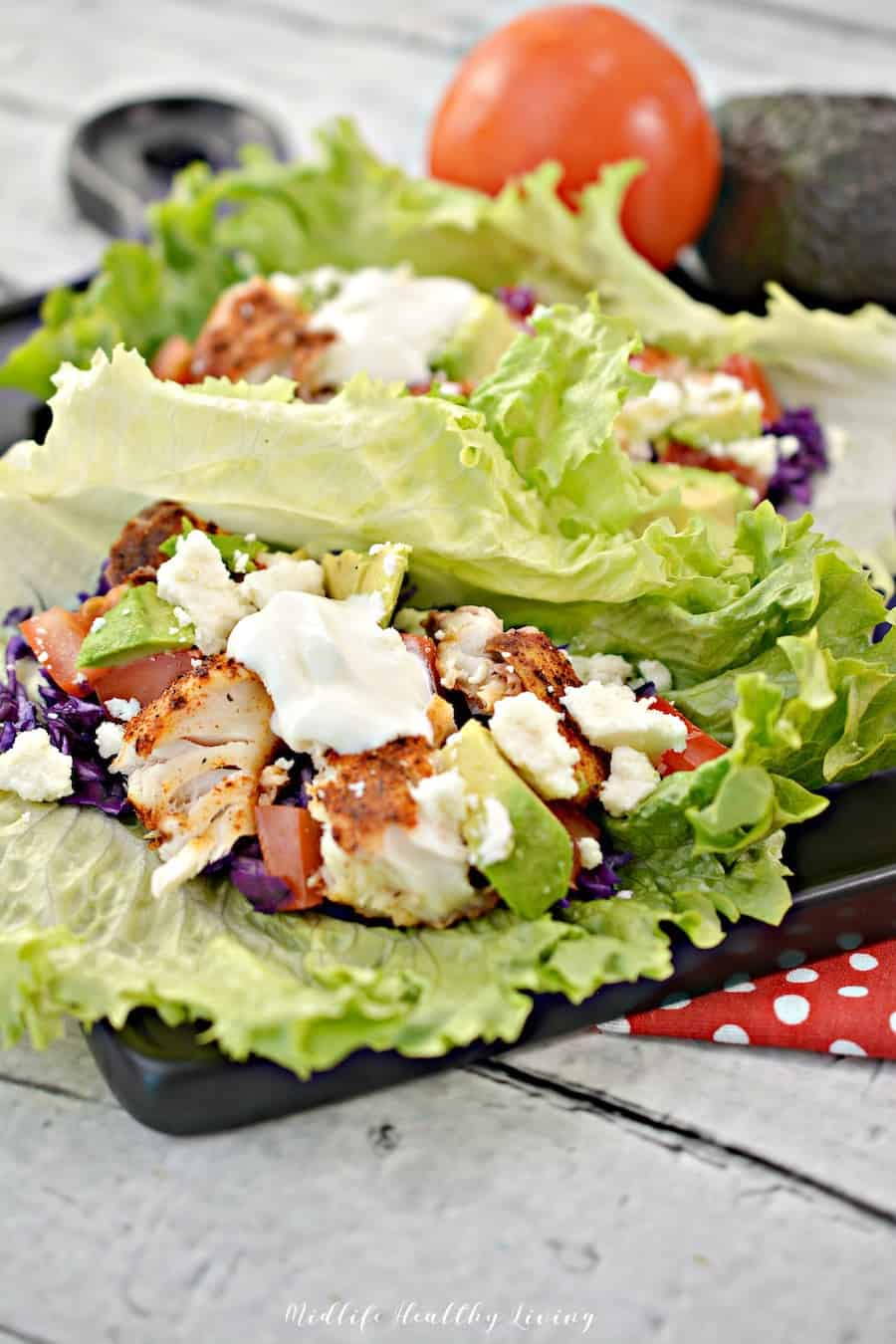 A great look at the delicious fish tacos served up on green leaf lettuce.