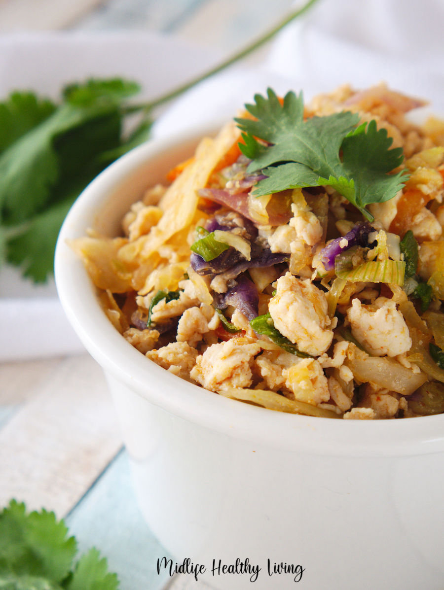 A horizontal view of the finished egg roll in a bowl with garnish ready to be served.