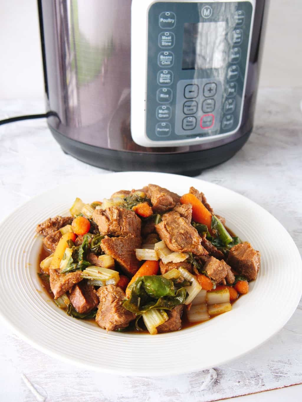 Finished beef stew recipe with the Instant Pot in the background.