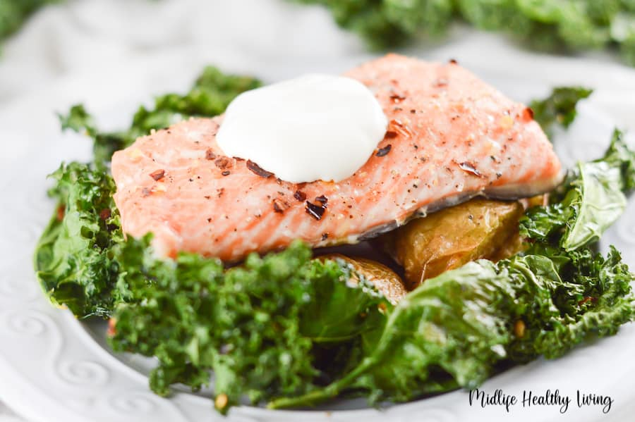 A close up shot showing the deliciousness of the salmon with the creamy yogurt sauce on top.