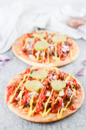 2 bacon flatbreads topped with meat ground meat, mustard and ketchup drizzle and 3 pickle slices.