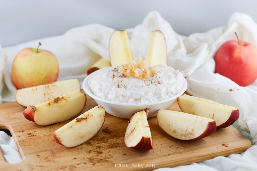 All the apples arranged around the bowl of dip ready to be enjoyed.