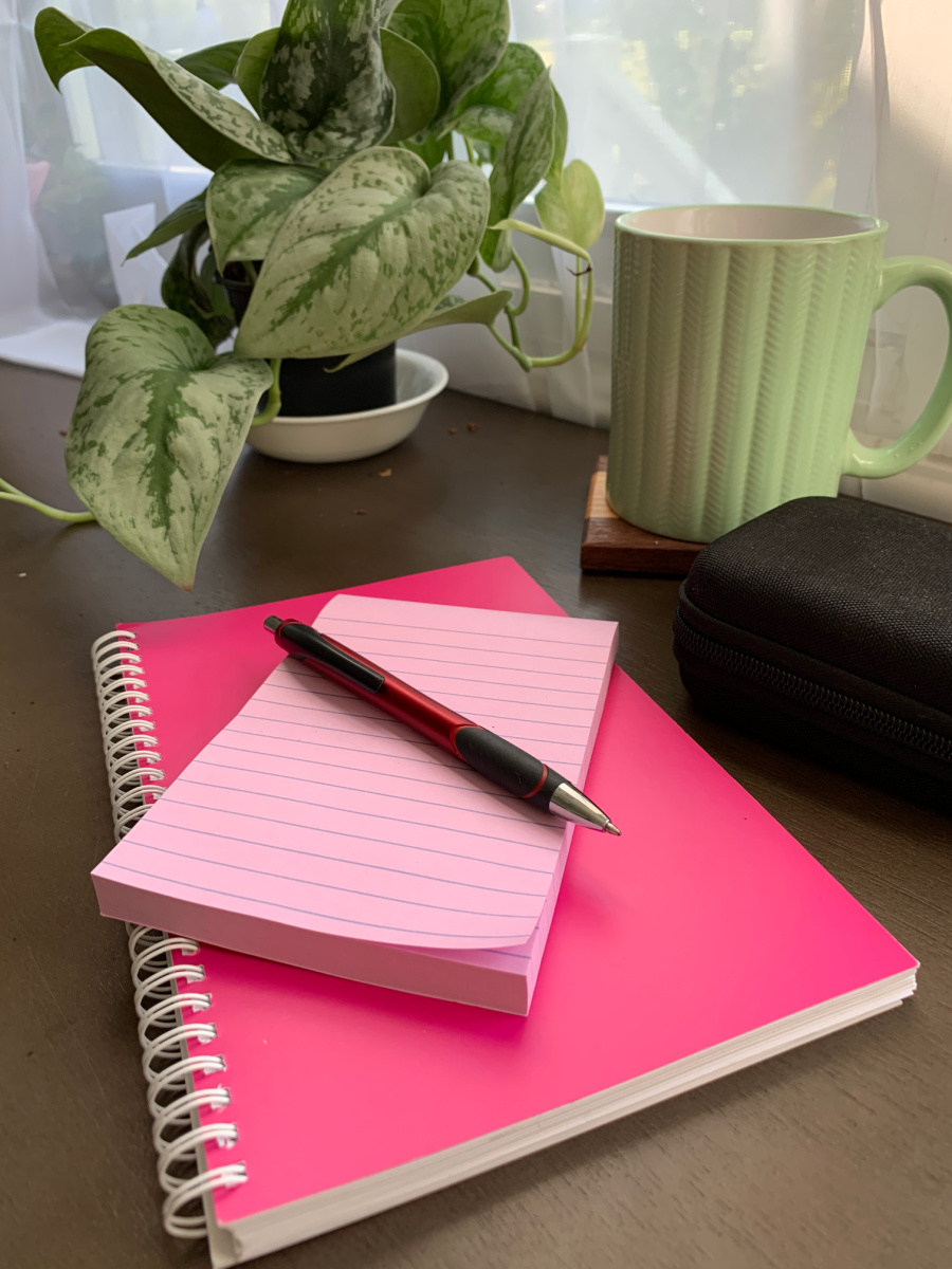 pink note book and pink note pad with a red pen on top