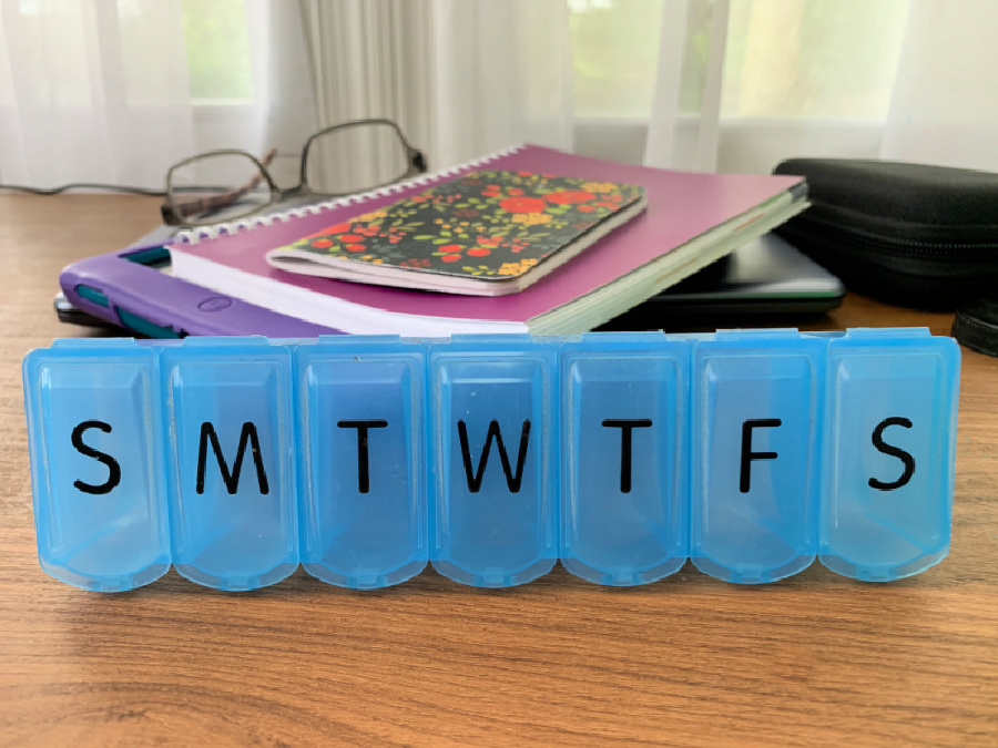 blue pill organizing box with the letters of the days of week on each compartment
