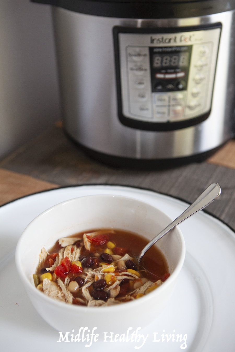 A finished bowl of the weight watchers taco soup ready to eat in front of the pressure cooker.