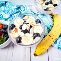 Featured image showing the finished weight watchers trifle recipe ready to eat with banana and berries lying beside the bowl.