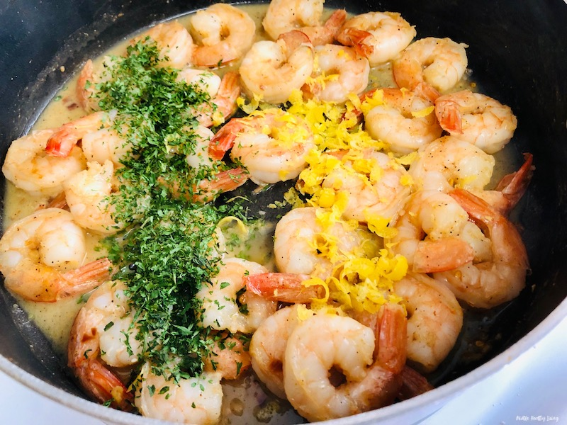Parsley and lemon zest being added to the finished shrimp.