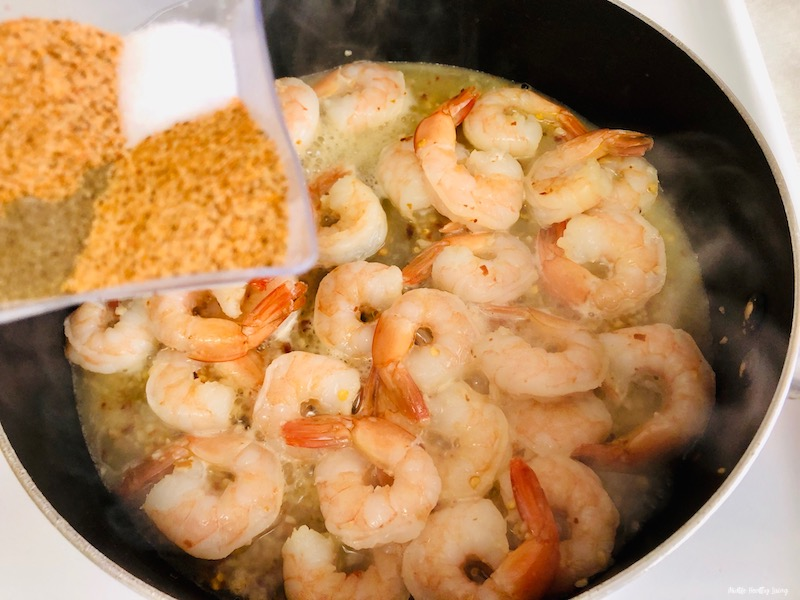 more seasoning being added to the plan of cooking shrimp.