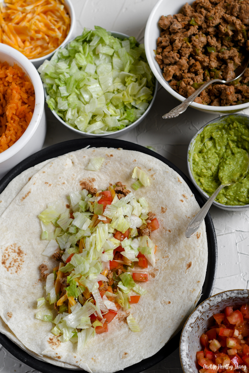 adding lettuce and tomatoes to the burrito before rolling.